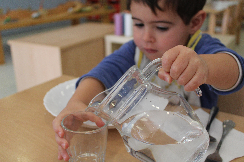 Imatge d'infant servint aigua