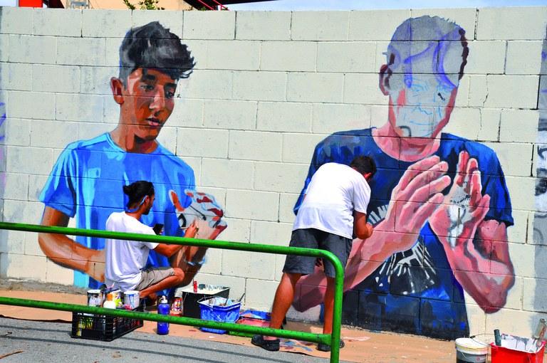 Pintant el mural commemoratiu del centenari del CF Ripollet al Camp de Futbol Municipal