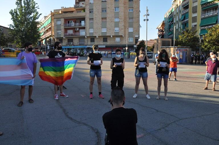 Proud LGTBI Ripollet llegint el manifest contra la LGTBI-fòbia amb les banderes de l'arc de Sant Martí i la bandera del col·lectiu Trans