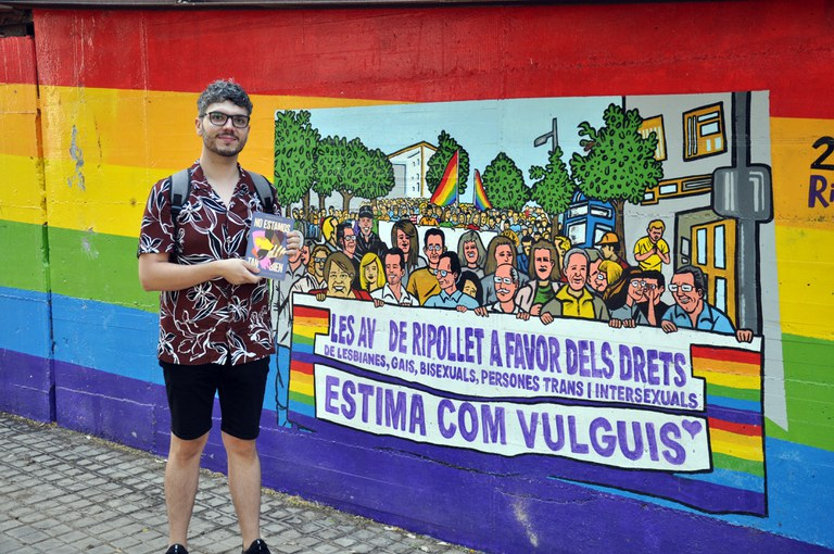 """Rubén Serrano davant el mural LGTBI amb el llibre """"No estamos tan bien"""""""